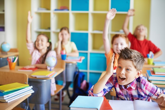 children-in-the-classroom-with-theirs-hands-up_1098-301